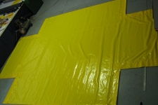 Yellow pvc tarp shaped to fit over machinery.